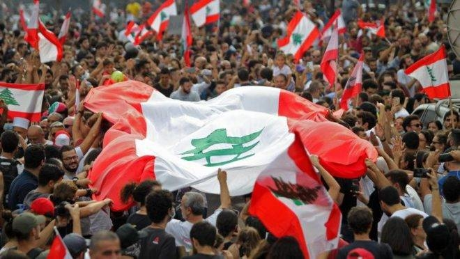 Lebanese demonstrators wave the national flag during a protest against dire economic conditions in downtown Beirut on October 18, 2019. - Public anger has simmered since parliament passed an austerity budget in July to help trim a ballooning deficit and flared on Thursday over new plans to tax calls on messaging applications such as Whatsapp, forcing the government to axe the unpopular proposal. (Photo by IBRAHIM AMRO / AFP)