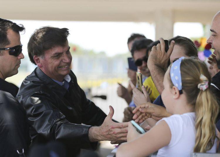 O presidente Jair Bolsonaro chega de moto no Palácio da Alvorada e cumprimenta turistas