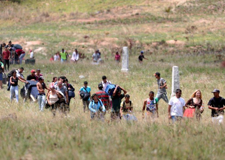 Pessoas caminham para tentar atravessar a fronteira entre a Venezuela e o Brasil em Pacaraima.