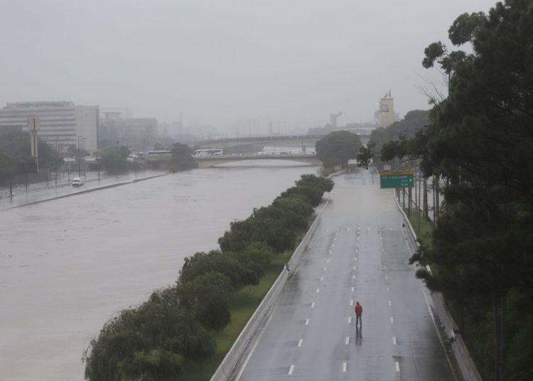 Um homem caminha sobre uma via expressa marginal parcialmente inundada do Tietê após fortes chuvas em São Paulo, Brasil, 10 de fevereiro de 2020. REUTERS / Rahel Patrasso