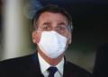 Presidente Jair Bolsonaro fala com apoiadores sem máscara e volta para colocar a sua que ficou no carro. Durante a conversa com os jornalista Bolsonaro colocou as mãos na máscara por mais de 6 vezes para arruma-la. Sergio Lima/Poder360 11.05.220