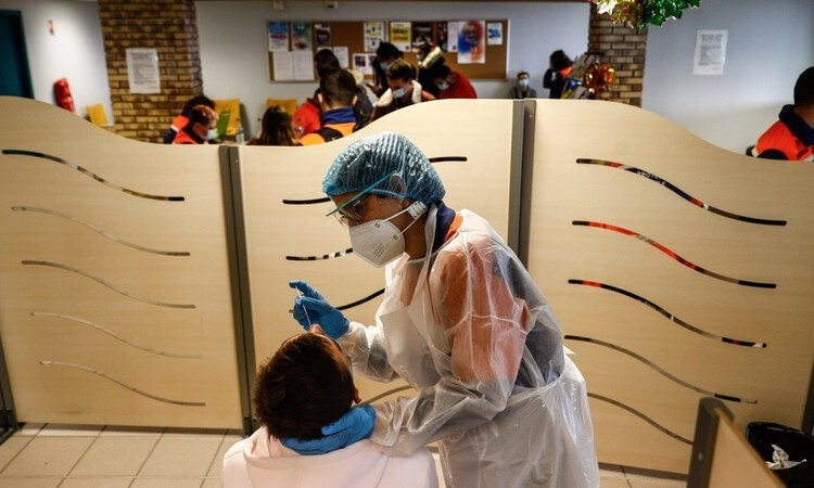 """A member of the Civil Protection takes a nasal sample with a swab from a student at an operation center for a Covid-19 mass testing campaign at a High School in Montivillliers, northern France on December 15, 2020. - In order to deploy the new """"Test, Alert, Protect"""" strategy, the health authorities wanted to be able to test all the new tools at the scale of territory by carrying out several massive testing campaigns. Four experiments, at the initiative of local authorities or ARS and with the support of the State, have thus been announced for the coming weeks: Le Havre, Charleville-Mezières, Roubaix, and Saint-Etienne. (Photo by Sameer Al-DOUMY / AFP)"""
