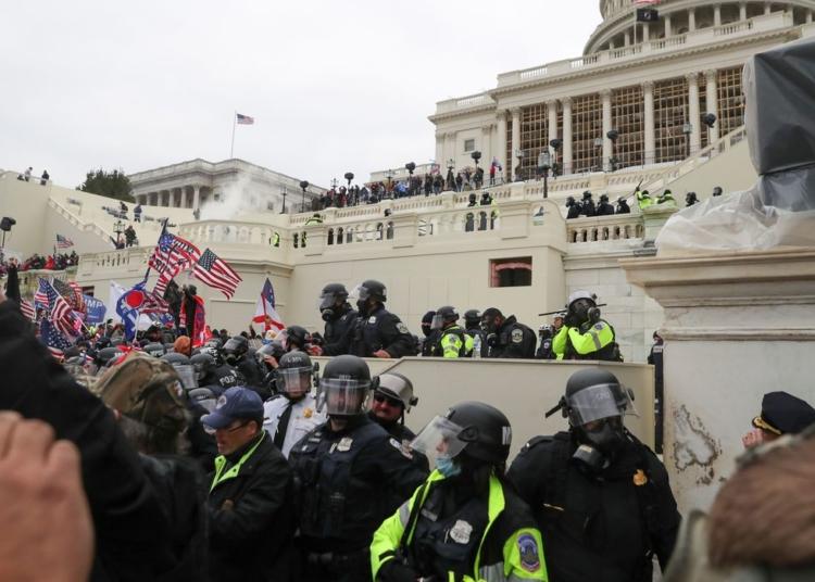 Policiais americanos montam guarda enquanto apoiadores do presidente norte-americano Donald Trumb protestam em frente ao Capitólio em Washington.