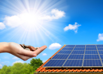 88570932 - solar panel on the roof of the house and coins in hand. the concept of money saving and clean energy.