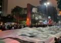 Foto: BBC NEWS BRASIL Legenda da foto, Bandeira é estendida na avenida Paulista enquanto manifestantes interditam os sois sentidos da via em SP